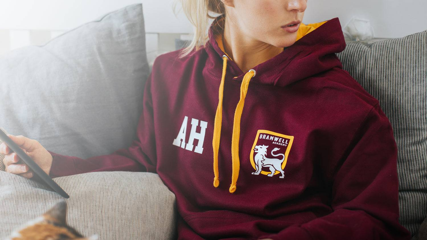 A girl sat in a burgundy leavers hoodie reading a Kindle