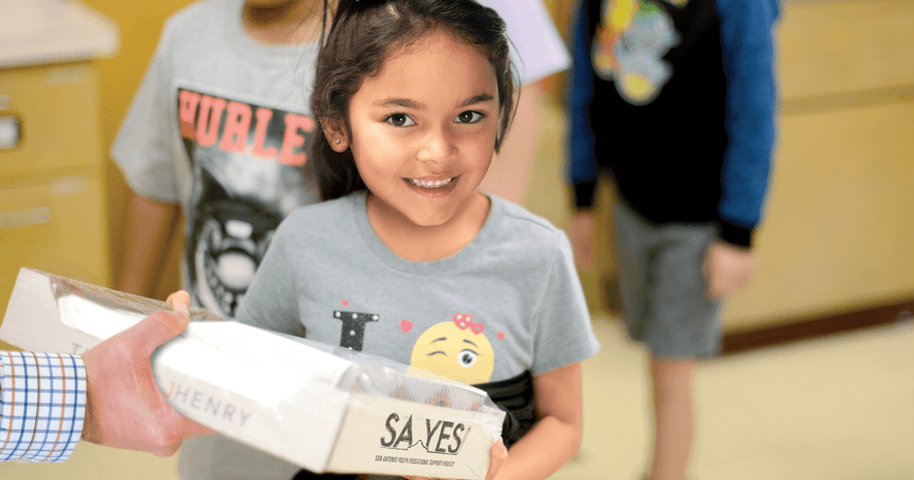 Image of an elementary student receiving a box of SA YES supplies