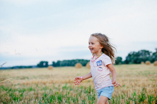 Menina correndo e sorrindo