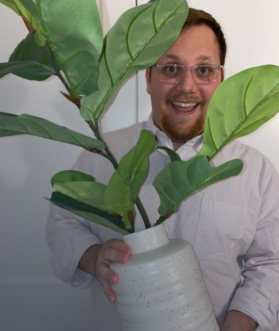 A picture of Nick holding a plant.