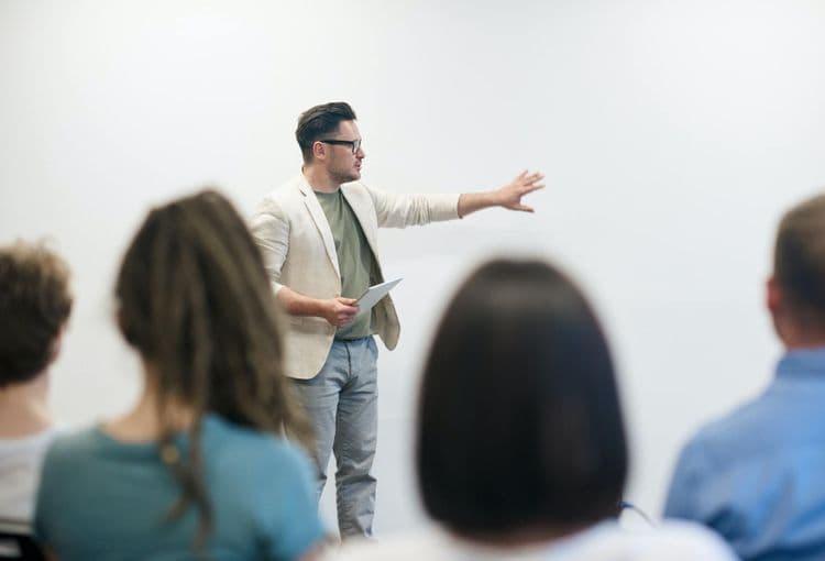 Lehrer erklärt Teilnehmern an Whiteboard eine Übung