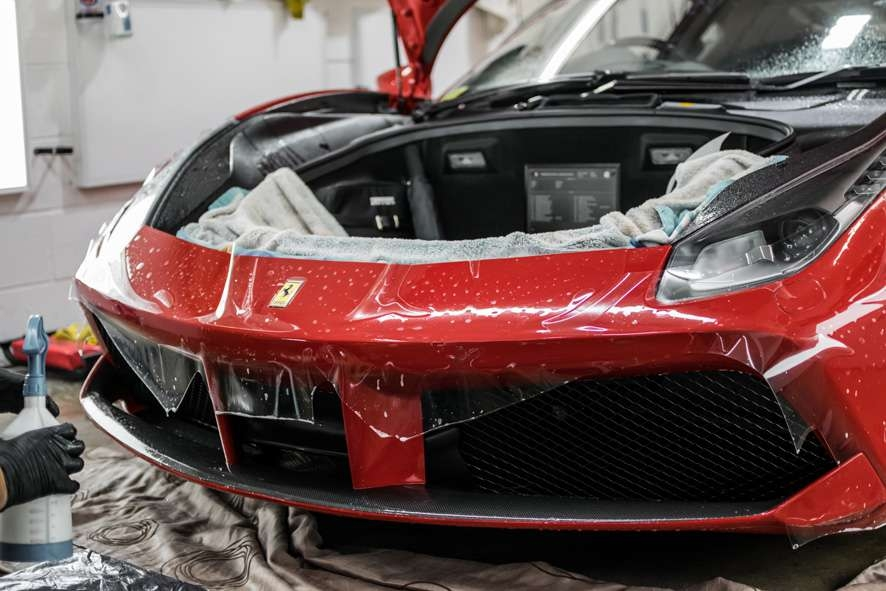 Paint protection film (PPF) being applied to front bumper of red Ferrari 458 GTB