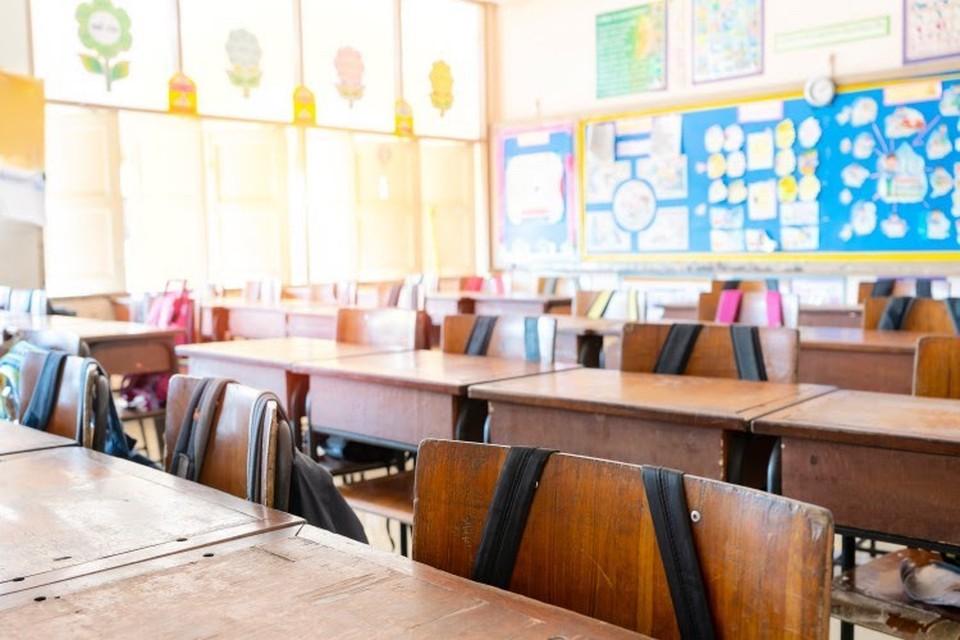 Backpacks hang on empty desks in a classroom.