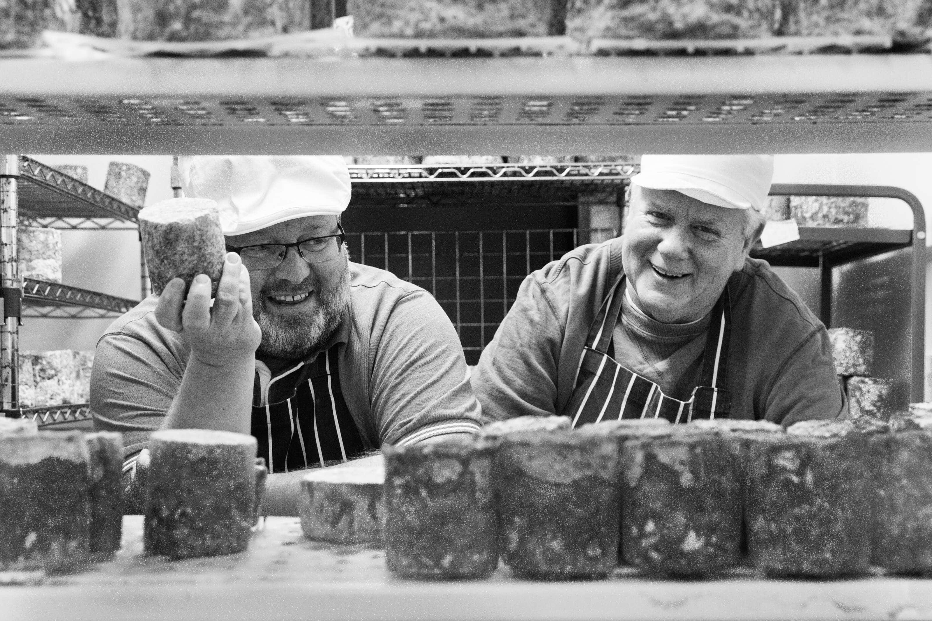 Philip and Keith, owners of Wildes Cheese of Tottenhams owners stood in one of the fridges holding Cheese and laughing.