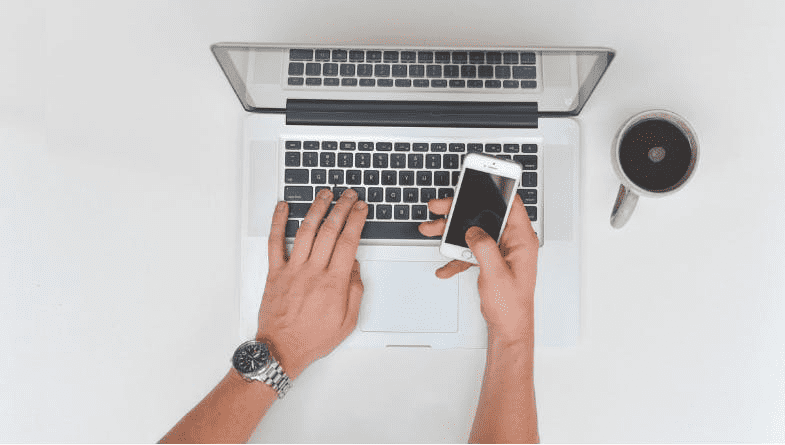Accountant holds phone whilst sat at laptop on white desk with a cup of coffee deciding when is best to use a phone call rather than an email #accountancy