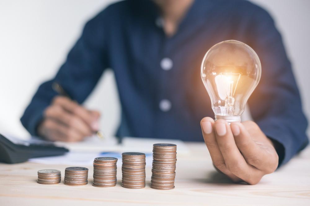 Mann mit Glühbirne in der Hand beim Geldzählen