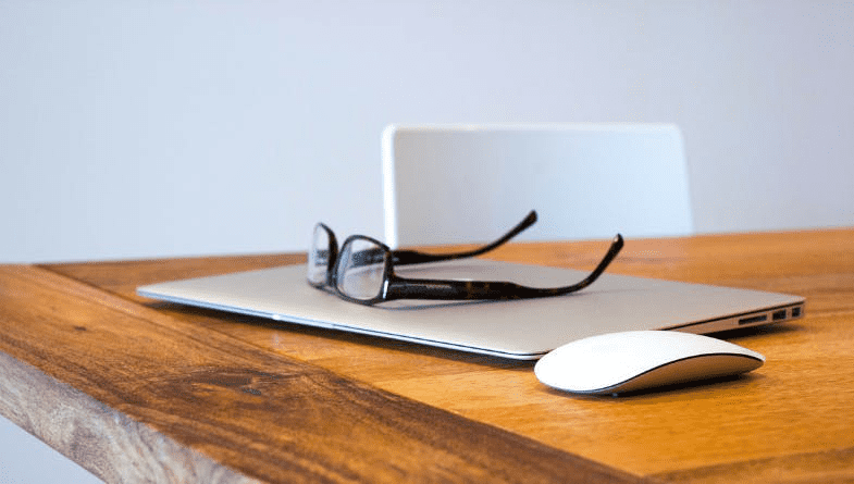 Glasses sit on laptop on wooden desk with mouse and chair in a paperless office #paperless