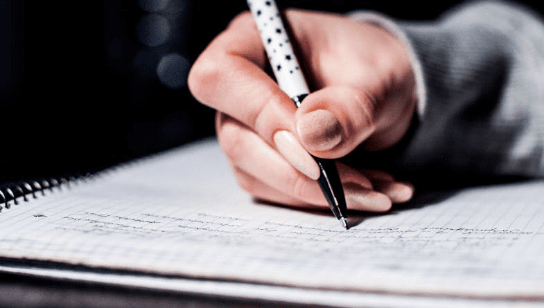Accountant writes with pen in notebook wearing grey suit. Uses 5 five tips for management accountants #productivity