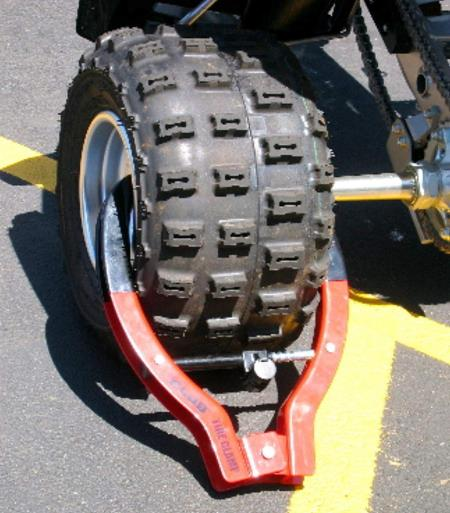 Winner International The Club 491 Tire Claw XL Security Device attached to a wheel.