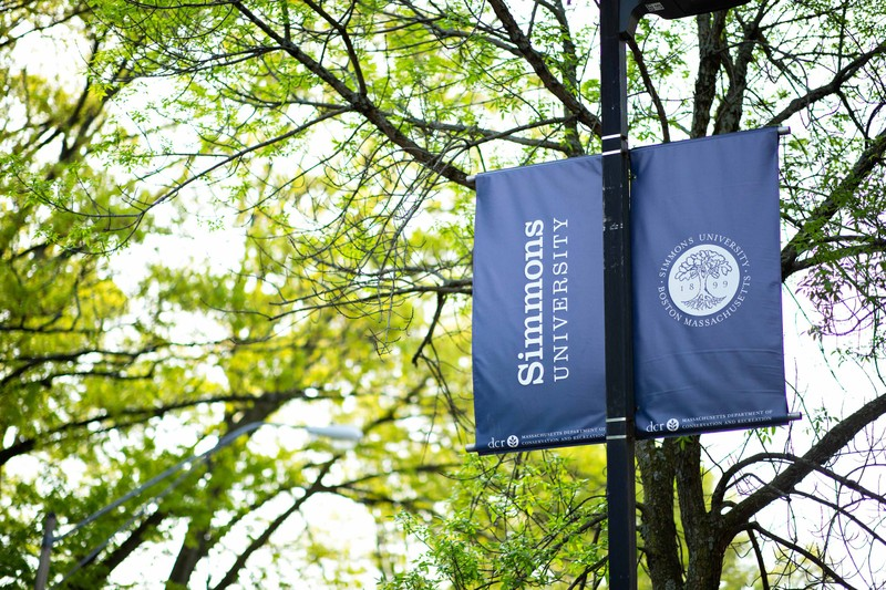 Simmons University flag attached to a light pole on campus