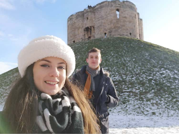 Myself and Naomi wrapped up in winter coats and scarves, stood in front of a snowy Clifford's tower