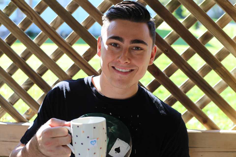 Hartley Watches Founder, Jeremy Hartley smiles at camera and holds up coffee mug sat on bench outside in garden and explains a day in the life and how he uses futrli and how to be a business owner #entrepreneur