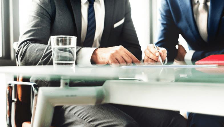 Man and woman, business owner and accountant, client, sit at desk with water, notebooks, pens, in suits, discuss a guide to management accounting #accounting