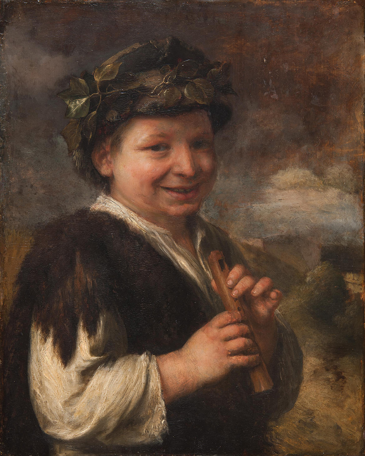 Portrait of a young boy smiling with recorder in hands wearing fur wrap and olive branches in his hair.