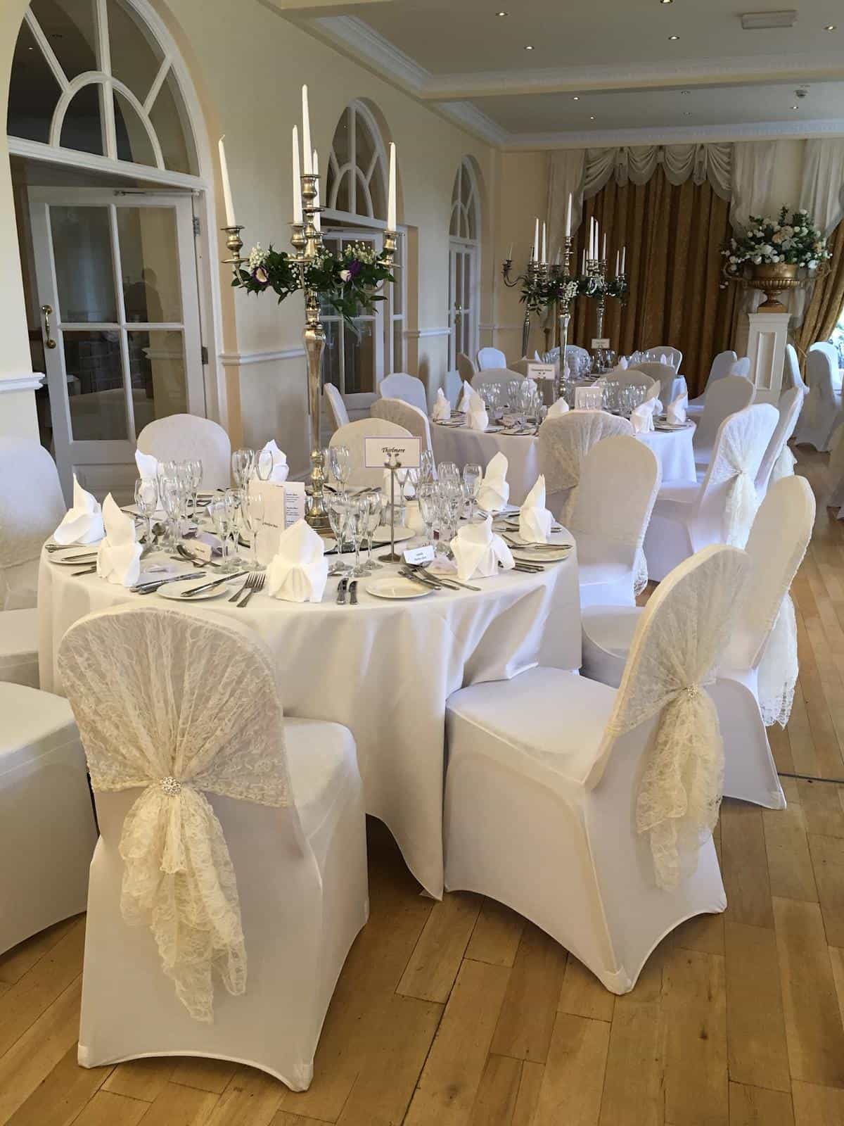 Wedding breakfast table with white table and chair linen with golden candelebra in centre and white lace hoods on backs of chairs