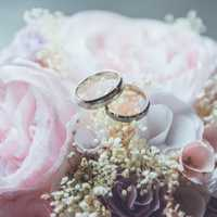 Photo of 2 wedding rings sitting on top of a wedding bouquet of light pink roses