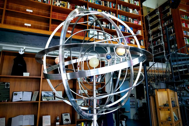 A spherical orrery made out of polished steal and stone at The Interval in San Francisco. Behind it are two floors of bookshelves and a spiral iron staircase.