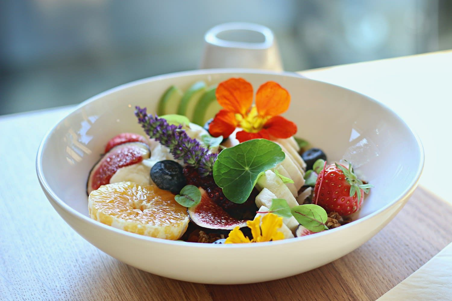Dignita brunch restaurant features healthy dishes like this bowl of fresh fruit and nasturtiums