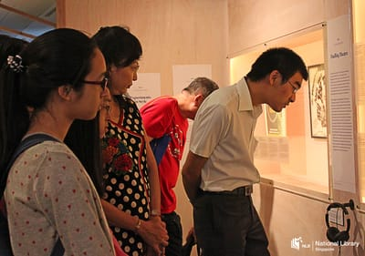 A photo of a tour at the exhibition. Visitors look into a wall showcase.