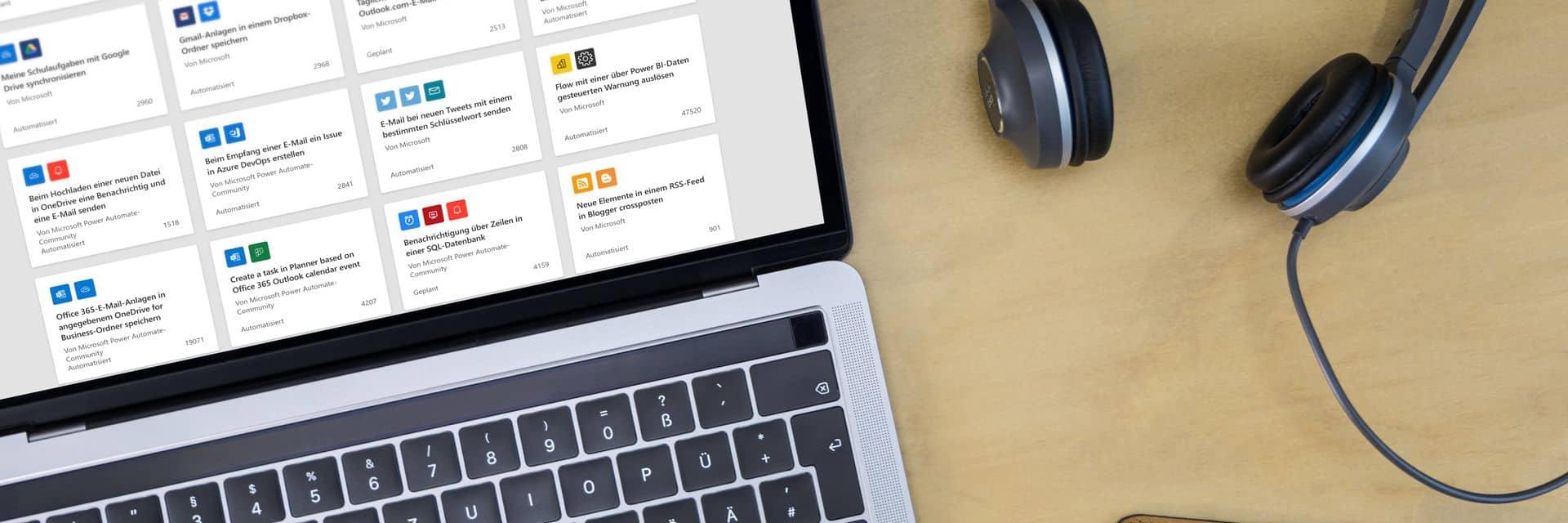 Laptop mit Power Automate, Smartphone und Kopfhörern