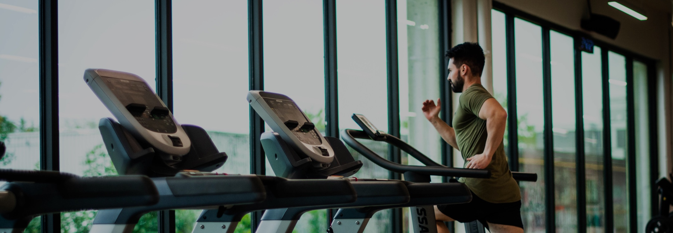 Image of athletic male on treadmill while using Les Mills video streaming mobile app.