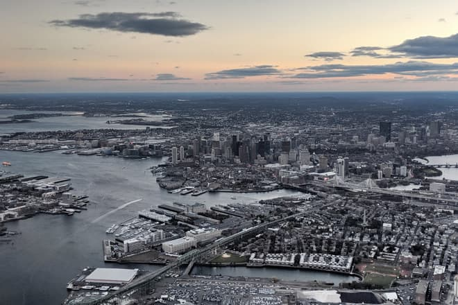 A city seen from the air at dusk. The Atlantic Ocean can just been seen on the left side of the frame.