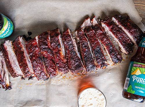 Plate of Sweet and Spicy Outburst IPA Ribs with a bottle of Pyramid Outburst
