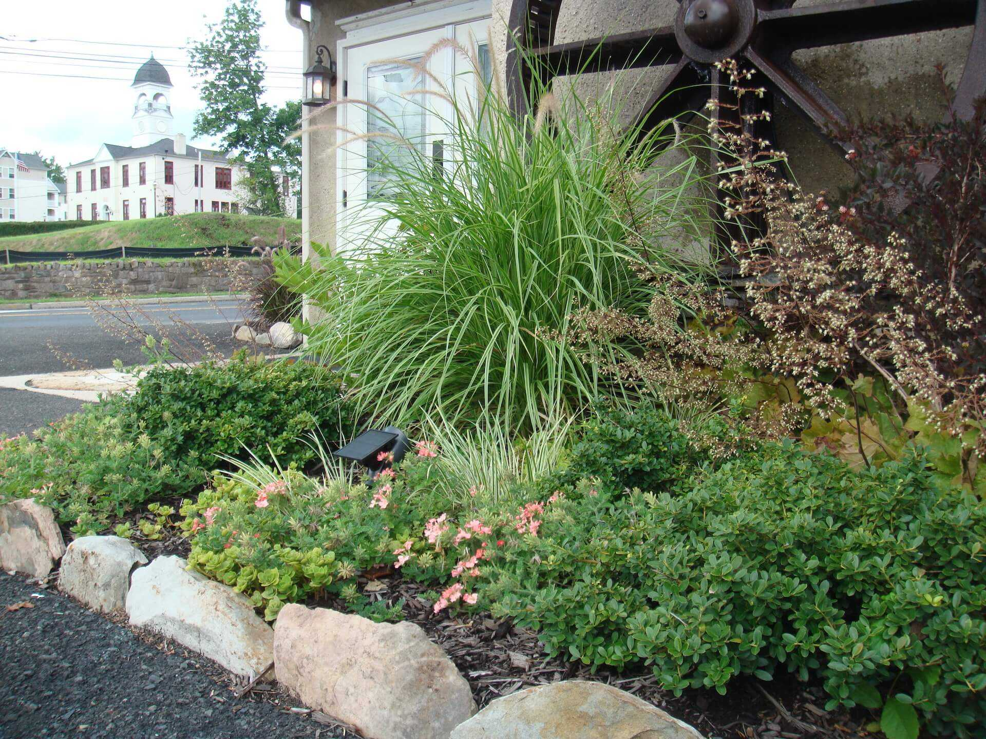 flowerbed in front of old fashioned wheel