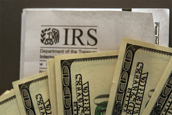 Hundred dollar bills in front of an IRS guideline publication.