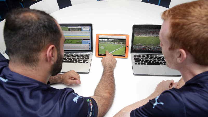 Two Sydney FC players watch soccer video footage analysis on two laptops and a tablet