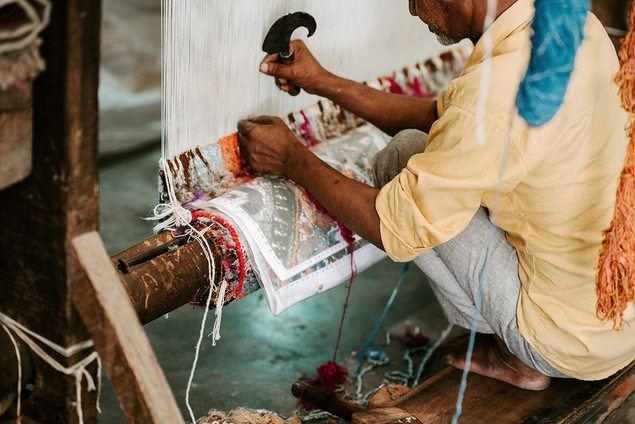 A man weaving a rug