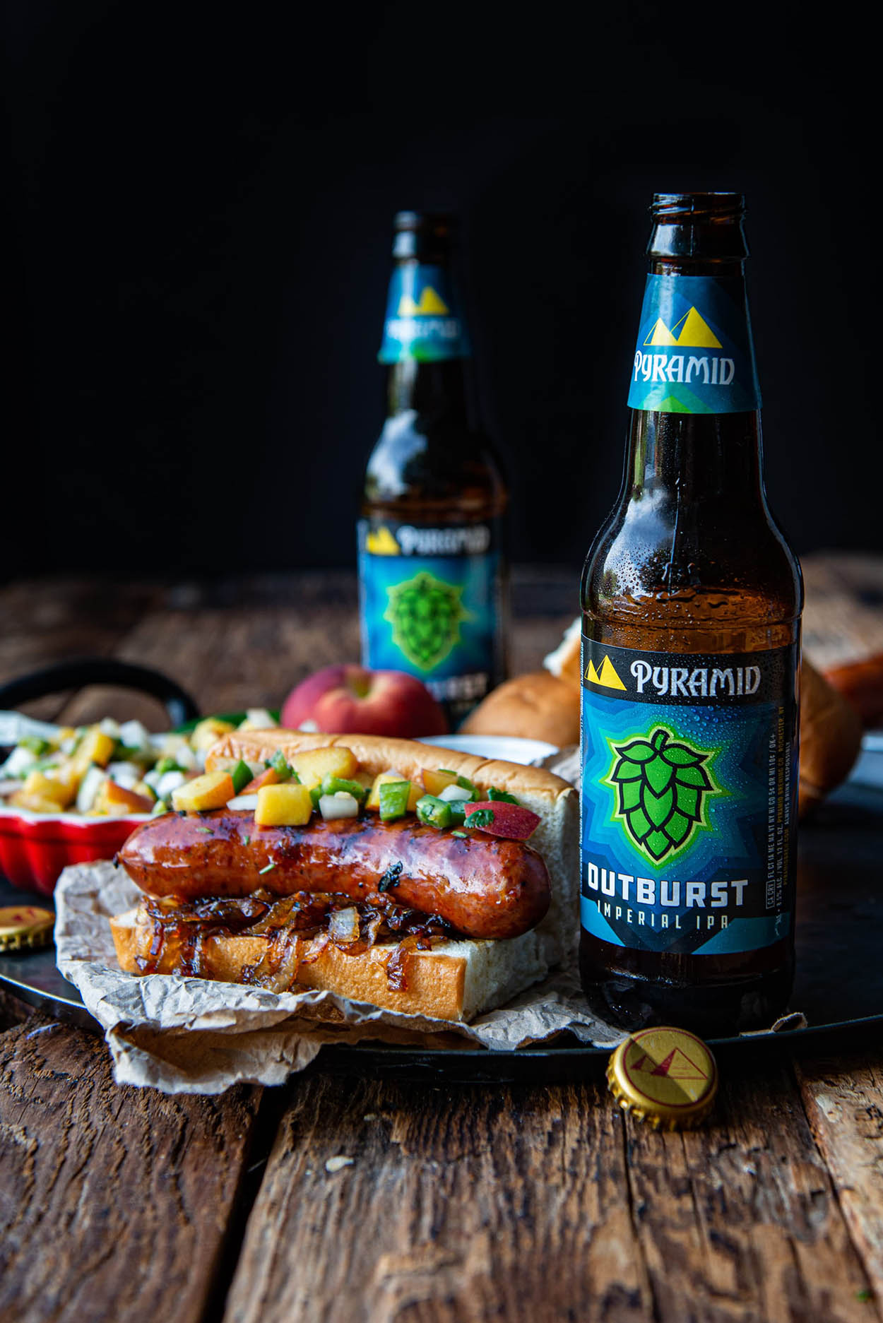 a photo of delicious homecooked bratwurst served with spicy homemade peach salsa and topped with carmelized onions, all served with a cold bottle of Outburst IPA