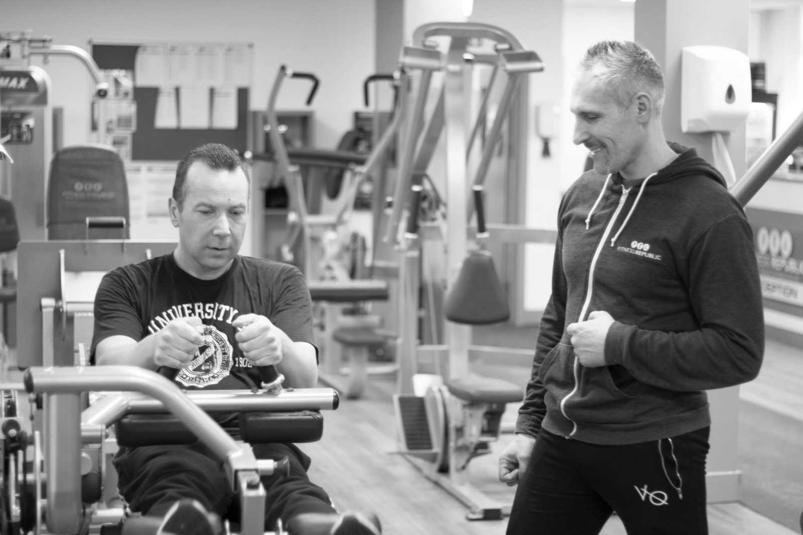 Black and white picture of to men in a gym