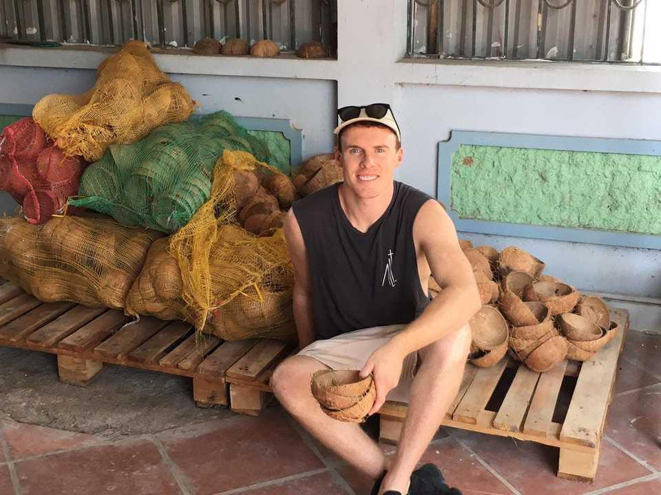 Jake McKeon with sunglasses, founder of coconut bowls, sits on wooden board in warm climate foreign country with a coconut in his hand and bags of coconuts behind him to tell how he uses futrli and a day in his life #Entrepreneur