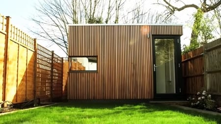 Backyard photograph showing this 'garden office pod', with vertical wood timber cladding and a second door into a storage area.