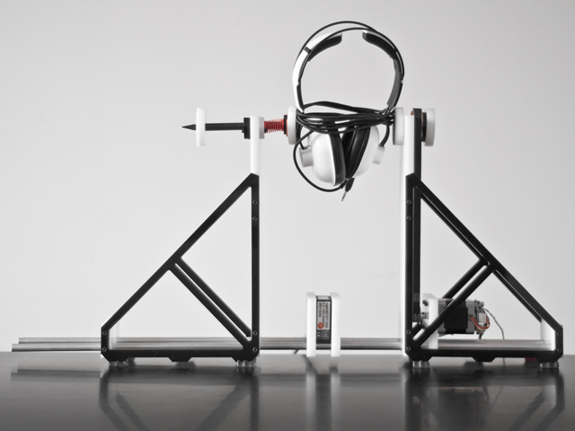 the same instrument, holding a large pair of headphones.