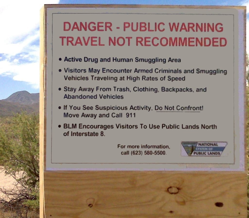 Arizona border sign: Danger - public warning. Travel not recommended. Active drug and human smuggling area. Armed criminals.