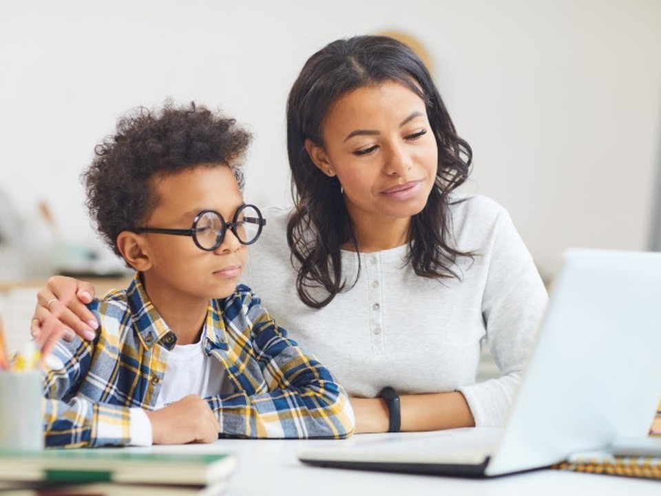 A mother and son work on a laptop as part of online learning.
