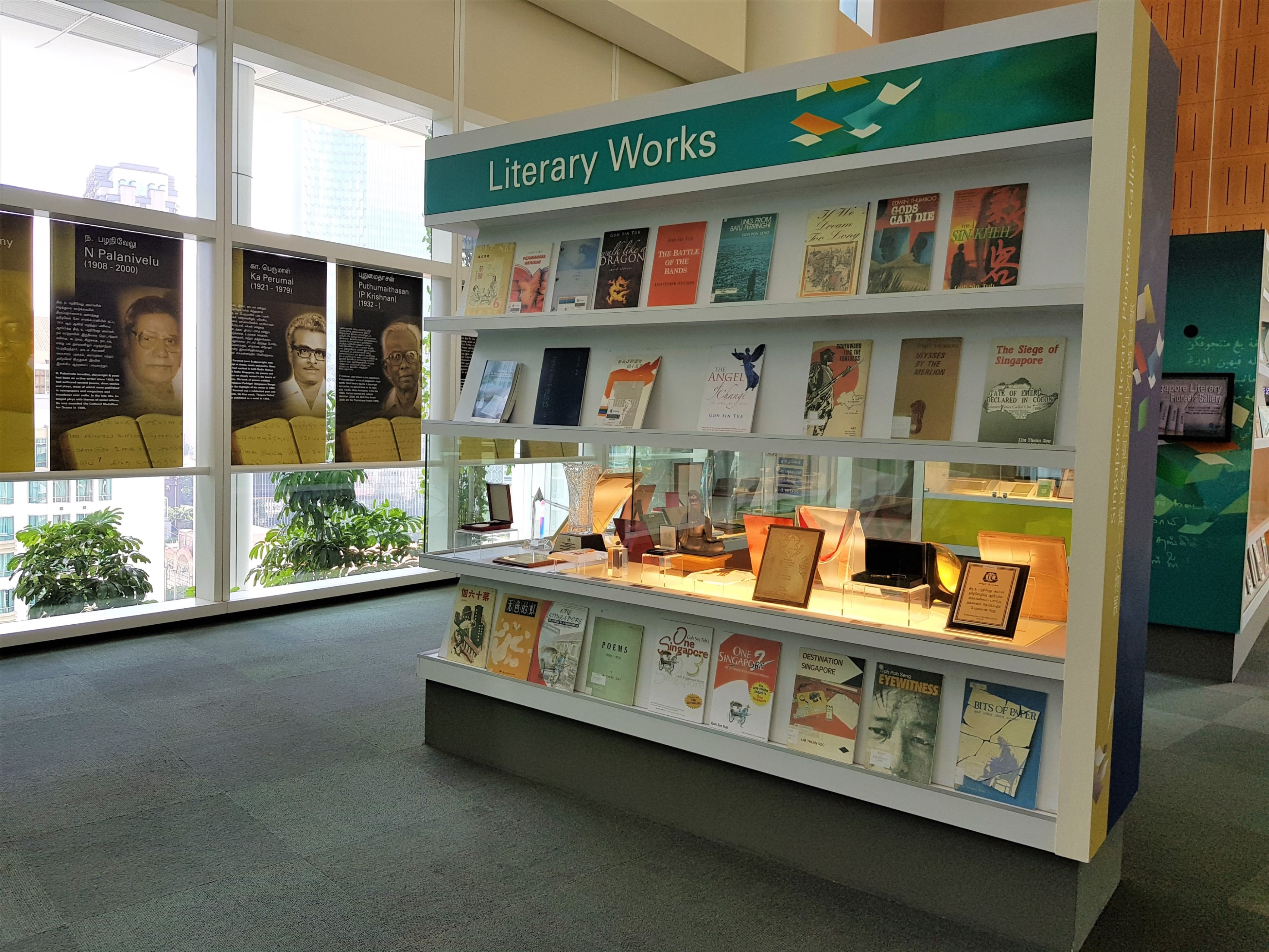 A wall title Literary Works. On the upper half, rows of illustrated book covers decorate the shelves. On the bottom half, there is a showcase featuring items of interest from the authors, such as trophies.