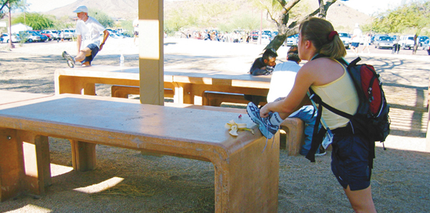 A woman uses a waist-high picnic bench to prop her foot so she can tie her shoe.