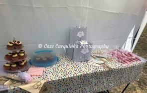 Table set up with cupcakes, baby girl presents and baby shower games