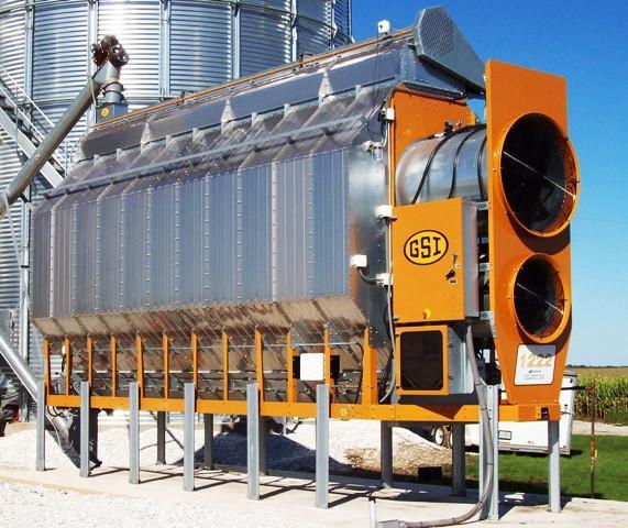A GSI grain dryer next to a grain silo.