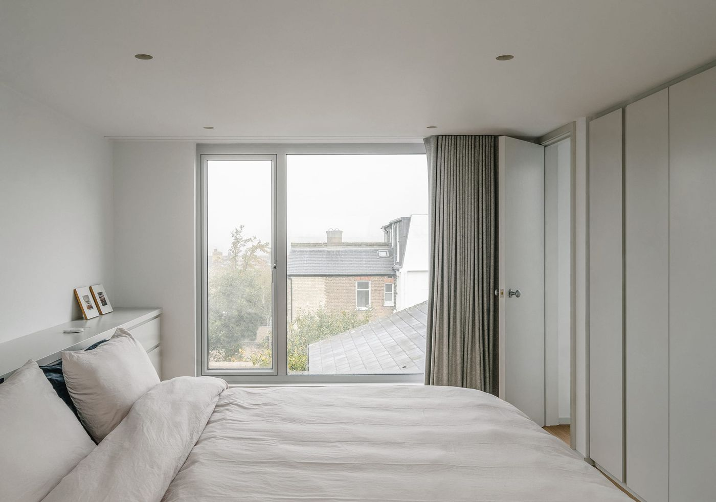 Internal view looking out of the large windows of the rear dormer extension with light grey joinery and lightweight curtains at Northbrook Road designed by From Works.