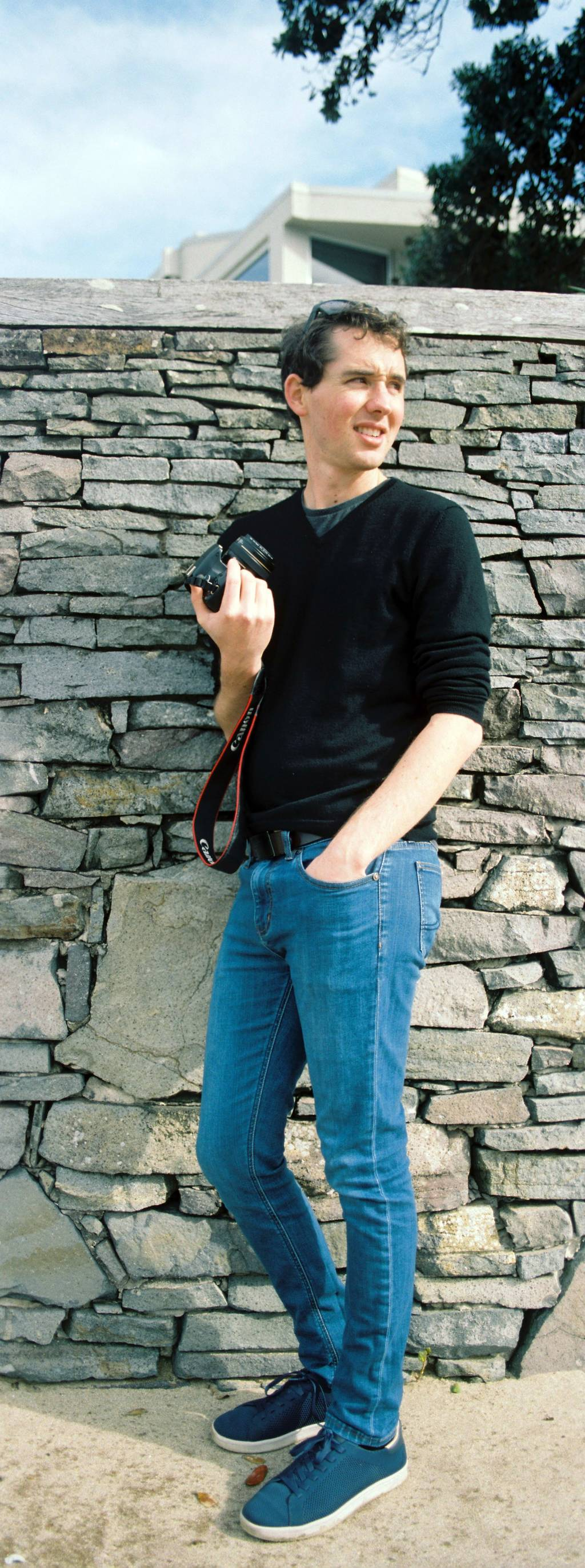 Vertical panorama of Byron posing with his camera up against a stone wall