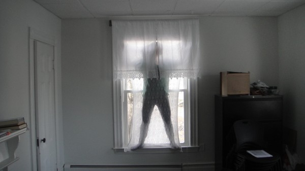 A body sock made from stretchy knitted lace, like so many front window curtains. The wearer steps inside the lace envelop and can disappear, perched in the window frame.