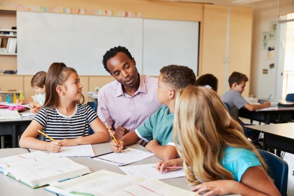 A teacher talks to three elementary school students who are working at a table in a diverse classroom setting.