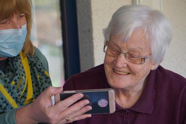 anciana mirando un movil y su cuidadora