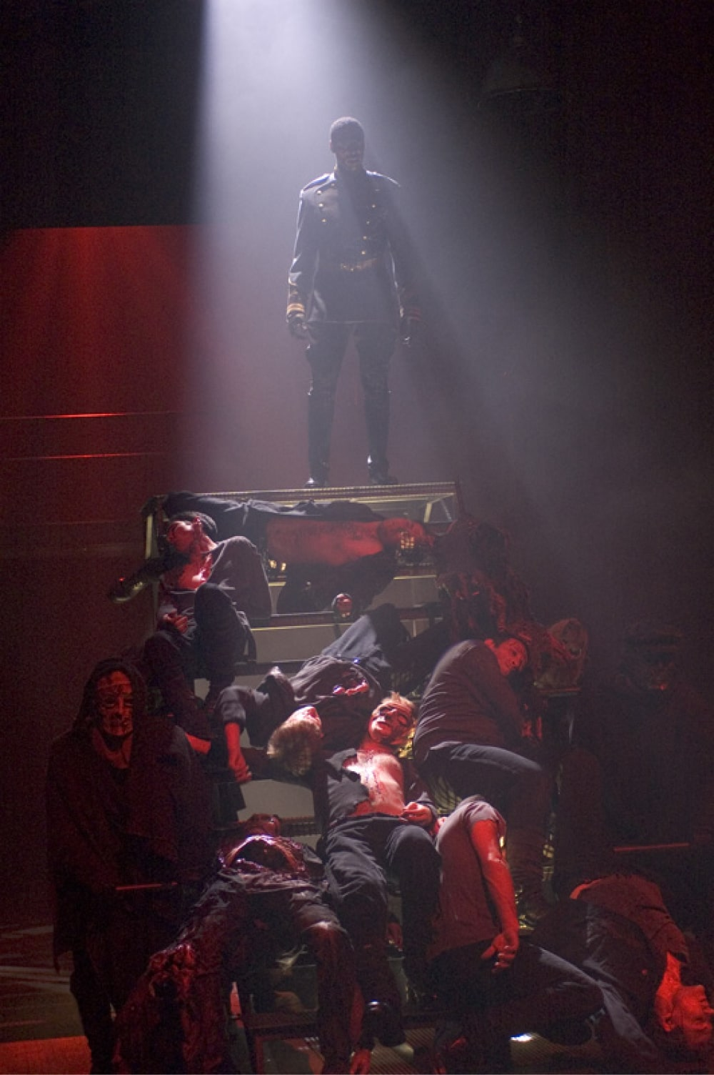 Soldier stands at top of staircase littered with dead soldiers in strong red back light.