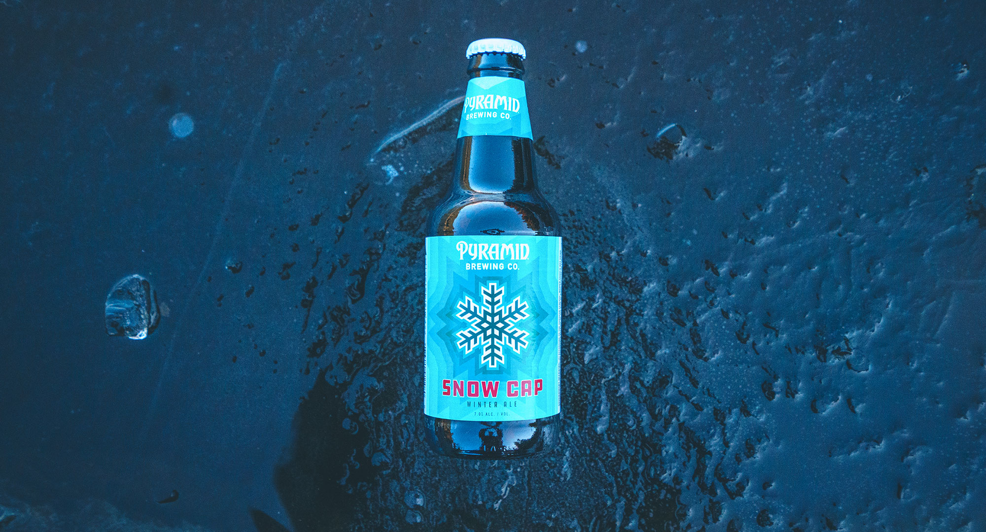 Looking down at a bottle of Snow Cap on frozen water