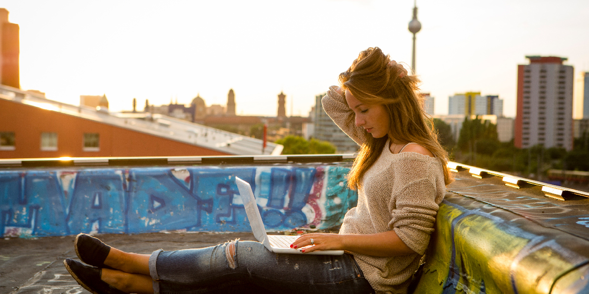 A remote  UX designer sitting on a Berlin rooftop with her laptop